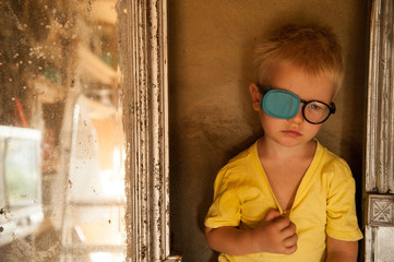 Child in glasses with occluder on background of old mirror. Ortopad Boys Eye Patches Nozzle for glasses to treat strabismus (lazy eye)