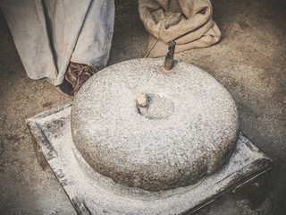 The ancient quern stone hand mill. Old grinding stones straw around