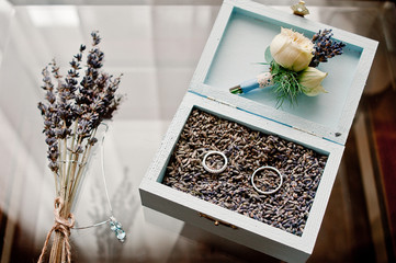 A sprig of lavender, a chain with a pendant, as well as wedding rings and a boutonniere in a beautiful wooden box on a glass transparent table