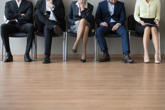 Close up businesspeople legs sitting in chair in queue wait job interview. Some of candidates sleeping, stressed tired and exhausted. Competition company position. Human resources, recruiting concept