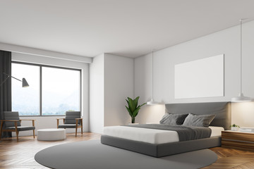 White bedroom, gray bed and poster