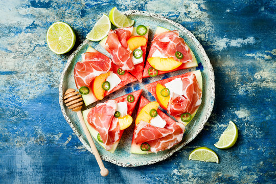 Fresh summer watermelon pizza with feta cheese, peach, prosciutto, jalapeno and honey drizzle on blue background