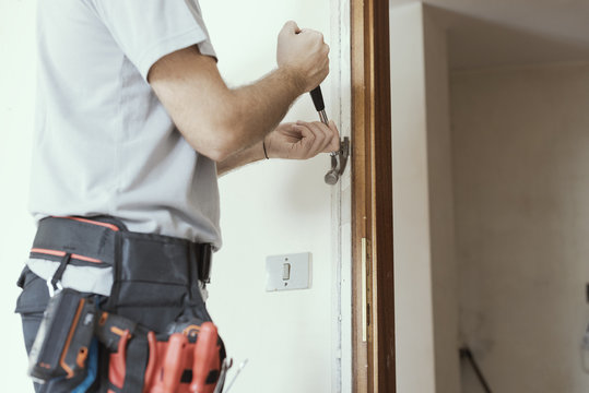 Carpenter removing an old door at home