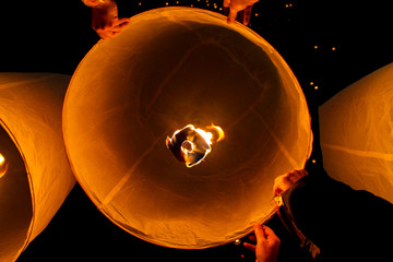 Group of people releasing sky paper lanterns on Ye Peng Festival in Chiang Mai, Thailand
