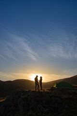 silhouette of couple on top of mountain at sunset