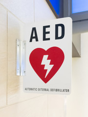 AED Automatic External Defibrillator sign on a wall with with a red heart and lightning bolt symbol.