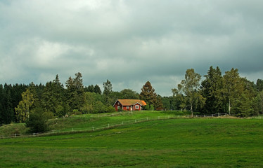 Red cottage and green fields with white fence