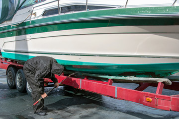 man wearing black waterproof rain suit while cleaning power boat hull with pressure washer