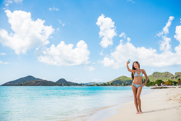 Wall Mural - Beach girl taking phone selfie on Caribbean vacation in Antigua. Cruise ship travel tourist Asian woman using cellphone on Jolly Beach, tropical island.