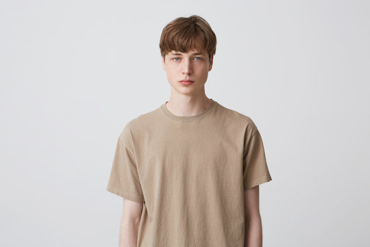 Portrait of serious handsome young man student with short haircut and blond hair in beige t shirt standing and looking directly in camera isolated over white background Feels concentrated
