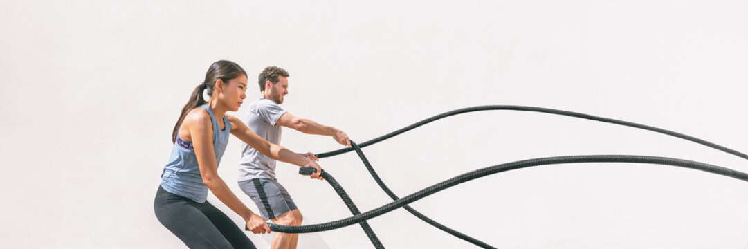 Gym fitness sport fit couple working out battle rope exercise banner panorama. Woman and man cross training amrs muscles and cardio with battling rope. Core workout panoramic crop.