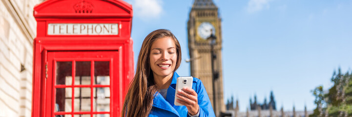 London phone woman walking on city street holding cellphone texting with british landscape, red telephone booth and Big Ben Clock Tower, London, England, UK. Banner panorama.