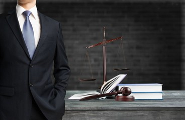 Lawyer standing near Scales of Justice on the background