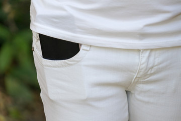 Mobile phone in the pocket of white pants.