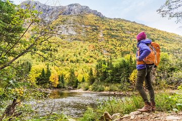 Wall Mural - Woman hiker hiking looking at scenic view of fall foliage mountain landscape . Adventure travel outdoors person standing relaxing near river during nature hike in autumn season.