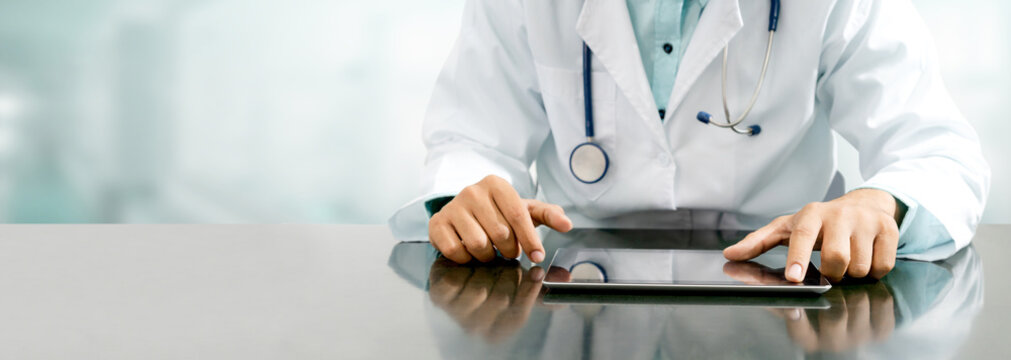 Doctor with tablet computer at hospital office.
