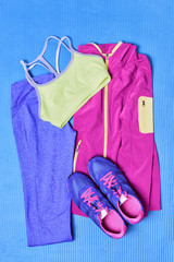 Pilates or yoga activewear fashion outfit to go train in gym . Fitness clothes on exercise mat with running shoes and blue leggings, cute girl clothes on background, top view.
