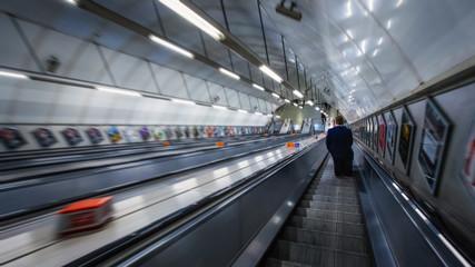 Unidentified people travel through underground train network in London, UK