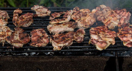 Grilling meats outdoors in a rustic old iron grill an hot coals for family gathering.