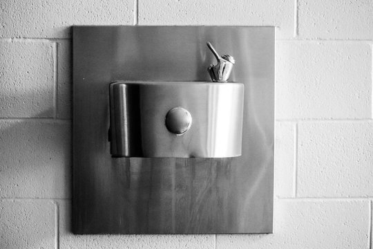 Black and white photo of water fountain attached to white washed brick wall