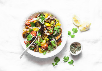 Roasted eggplant, sweet tomato and cilantro mediterranean style salad on light background, top view. Vegetarian food concept