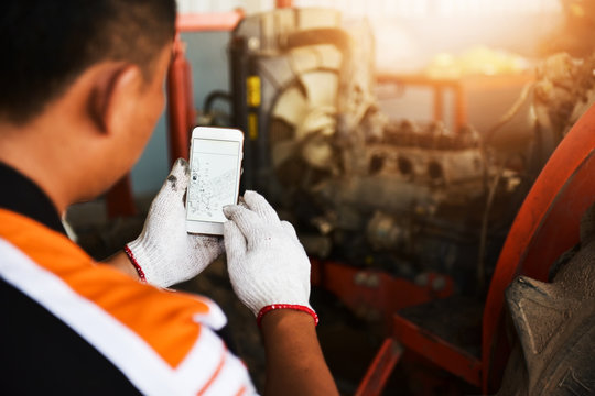 Hand Technician uses smart phone memory to check the list of vehicles using the connection technology system in agricultural tractors.