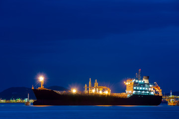 cargo ship at cargo terminal in harbor at night.