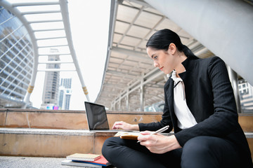Business concept. Young businesswoman is working in business district. Young businesswoman happy to work.