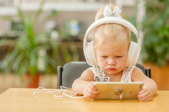 little girl watching cartoons on phone in headphones. Space for text
