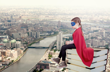 Superhero kid sitting on a stack of books against urban background. Girl power concept