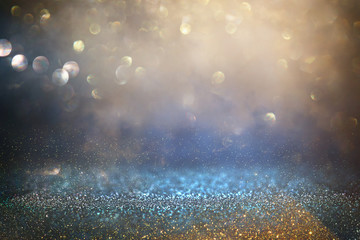 glitter vintage lights background. black, blue and gold. de-focused.