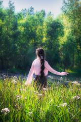 Young girl in summer sunny day walking and dancing in fields flowers