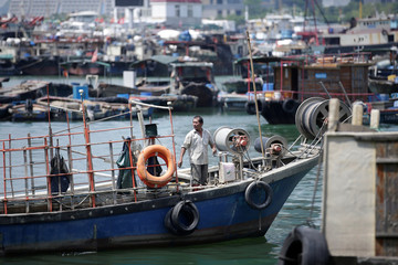 A fisherman prepares to anchor a boat at a fishing harbour, as Typhoon Mangkhut approaches, in Shenzhen