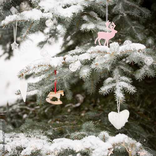 Close up of snowy Christmas tree with nice decorations in the forest. Winter, Christmas celebration, holidays season.