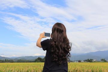 スマートホンで写真を撮る女性 田舎 ひとり旅 イメージ