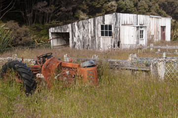 Derelict, overgrown, rusty tractor in the foreground with an abandoned building in the background. On the walk from Mason Bay across Stewart Island, Rakiura, New Zealand.