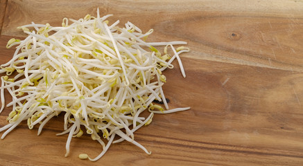 Bean sprouts on a wooden chopping board.