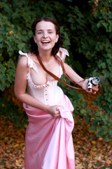 Fine emotional brunette with vintage photo camera. Yonge girl in vintage pink pastel with live expressions on beautiful country and old background.