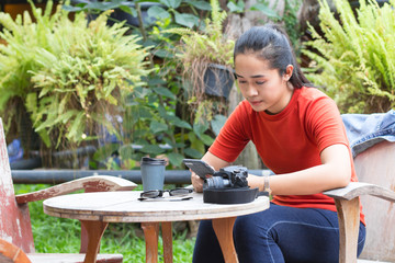 Women are playing internet on mobile phones and have a camera, sunglasses, a coffee cup is on a wood table.