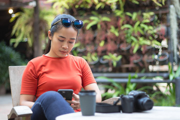 Women are playing internet on mobile phones and have a camera, a coffee cup is on a wood table.