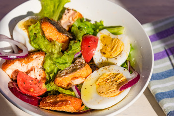 Healthy diet salad with salmon, tomatoes, eggs, onion and lettuce, top view. Dietary lunch