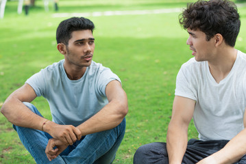 Serious Indian guy sharing problem with friend in summer park. Handsome young men sitting on grass and talking. Chatting concept