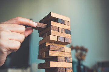 Closeup image of a hand holding and playing Jenga or Tumble tower wooden block game