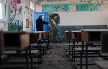 Palestinian man gestures as he inspects a classroom of a United Nations-run school that was damaged in Israeli shelling, in Khan Younis in the southern Gaza Strip