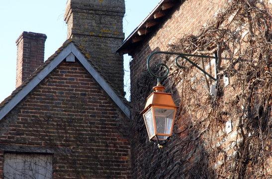 Ville de Rugles, lanterne dans les rayons du soleil accrochée au mur, département de l'Eure, Normandie, France