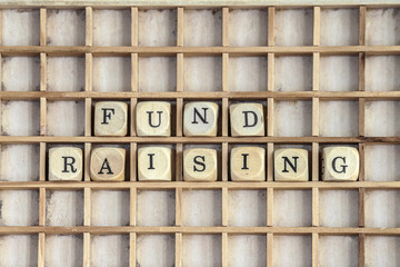 Fund raising sign made of dices on a dirty shelf