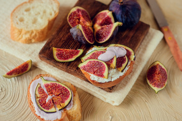 Autumn dessert: sweet toast with ripe figs, soft cheese and honey on a light background.