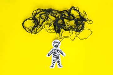 Negative thinking  concept, paper man and black thread on the yellow background.