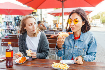 Woman eating Currywurst fast food German sausage in outdoor street food cafe