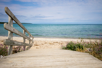 Path To The Beach. Wooden ramp leads to a wide sandy beach with a blue water horizon on a sunny sandy beach along the Great Lakes coast.